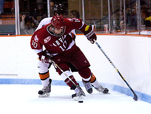 Eric Kroshus (Harvard - 10) plays the puck along the boards away from Derrick Pallis (Princeton - 5). (Shelley M. Szwast)