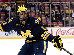 Michigan forward Kevin Lynch picks at the puck in Michigan Tech's zone. (Erica Treais)