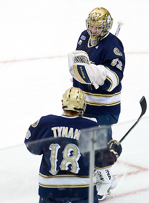 Notre Dame's T.J. Tynan and goaltender Mike Johnson celebrate a goal. The University of Minnesota-Duluth Bulldogs defeated the University of Notre Dame Fighting Irish 4-3 in the opening semi-final of the 2011 Frozen Four at Xcel Energy Center in St. Paul, Minnesota. (Melissa Wade)