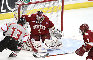 Denver's Paul Phillips is able to poke the puck away from UNO's Zahn Raubenheimer as goalie Sam Brittain defends the goal. Denver beat Nebraska-Omaha 4-2 Saturday night at Qwest Center Omaha. (Photo by Michelle Bishop) (Michelle Bishop)
