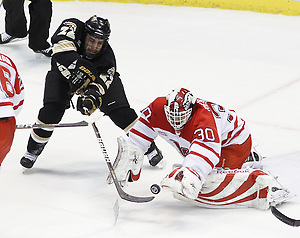 Western Michigan Left Winger Derek Roehl tries to deflect a puck past a diving Miami goalie Cody Reichard during the first period of the CCHA Championship game at Joe Louis Arena on Saturday, March 19, 2011. (Rena Laverty)