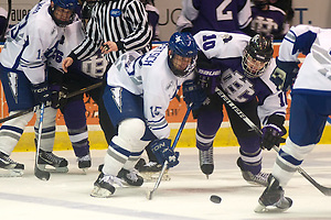 Sean Bertsch (15, white) and Kyle Fletcher (10) fight for a loose puck. (2011 Omar Phillips)