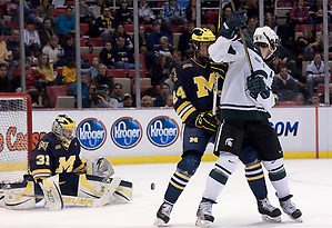 Michigan State assistant captain Trevor Nill and University of Michigan's Jon Merrill look for the puck in front of the Wolverine goal. The Spartan's came out with a 2-1 win; Joey Shean scored the game winning goal with less than seven minutes left in the game. (Erica Treais)