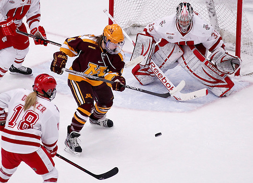 Minnesota's Becky Kortum battles between Wisconsin's Brianna Becker (18) and goalie Alex Rigsby during the first period of an NCAA college hockey game Friday, Jan. 25, 2013, in Madison, Wis. (AP Photo/Andy Manis) (Andy Manis/AP)
