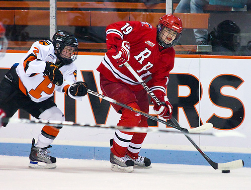 Jordan Smelker (RPI - 19) plays the puck along the boards as Kelly Cooke (Princeton - 2) gives chase. Rensselaer visited Princeton's Hobey baker rink, falling to the Princeton Tigers 4-2. (Shelley M. Szwast)
