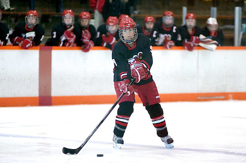 Allison Era of Plattsburgh controls the puck on the power play as her teammates look on from the bench (2012 Omar Phillips)