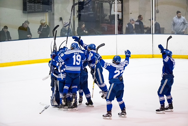 Colby Mules celebrate a win after scoring a second goal with 1.6 second remaining in regulation against the Geneseo Knights at the NCAA Division III men's ice hockey Tournament Second-Round between the Geneseo Knights and the Colby Mules on March 17, 2018. Collby defeats Geneseo 2-1. Photograph by Brett Carlsen for Colby College. (Brett Carlsen)