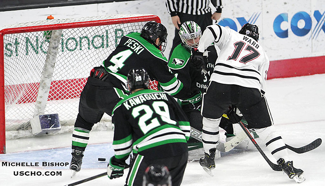 Nebraska-Omaha's Taylor Ward (17) sends the puck past North Dakota goalie Adam Scheel during the third period. Nebraska-Omaha beat North Dakota 4-3 Saturday night at Baxter Arena. (Photo by Michelle Bishop) (Michelle Bishop)