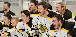 AIC players await the Atlantic Hockey championship trophy (2019 Omar Phillips)