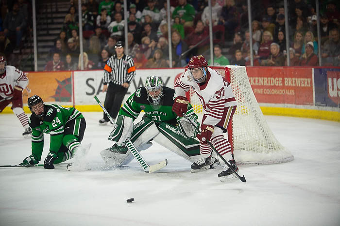 Adam Scheel of North Dakota looks at the puck while Denver's Hank Crone sizes up a rebound, North Dakota vs. Denver at Magness Arena, Nov. 15, 2019. (Candace Horgan)